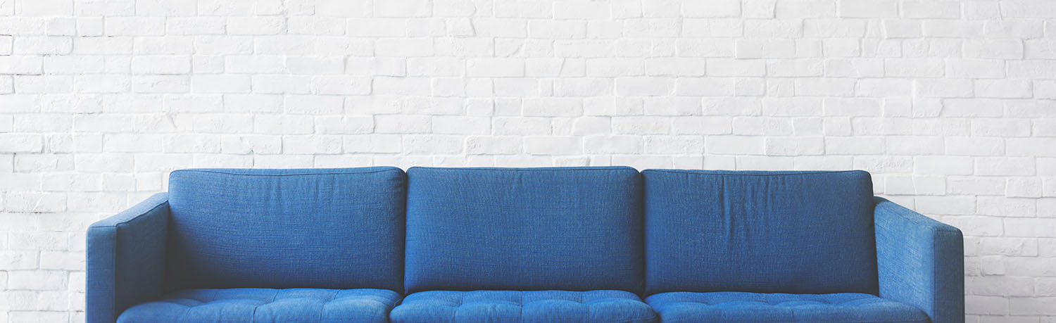 room with white walls and a blue sofa
